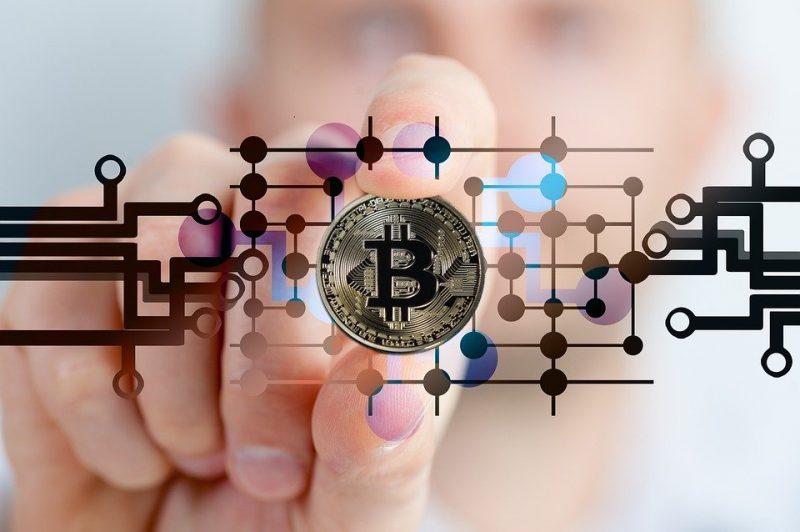 Physischer Bitcoin mit Hand und digitalen Daten